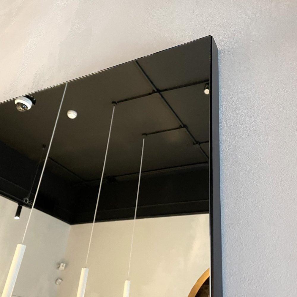 Настенное зеркало в черной раме